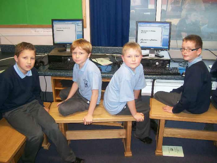 P7 pupils tutoring P4 in ICT.